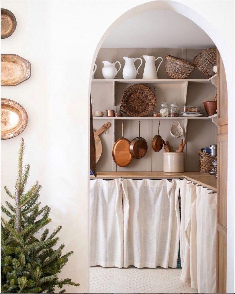 European style pantry with linen curtains and arched entryway