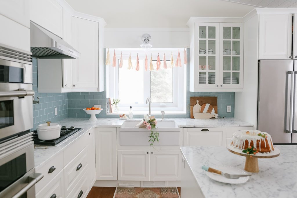 A kitchen with a sink and a window decorated with a banner and flowers