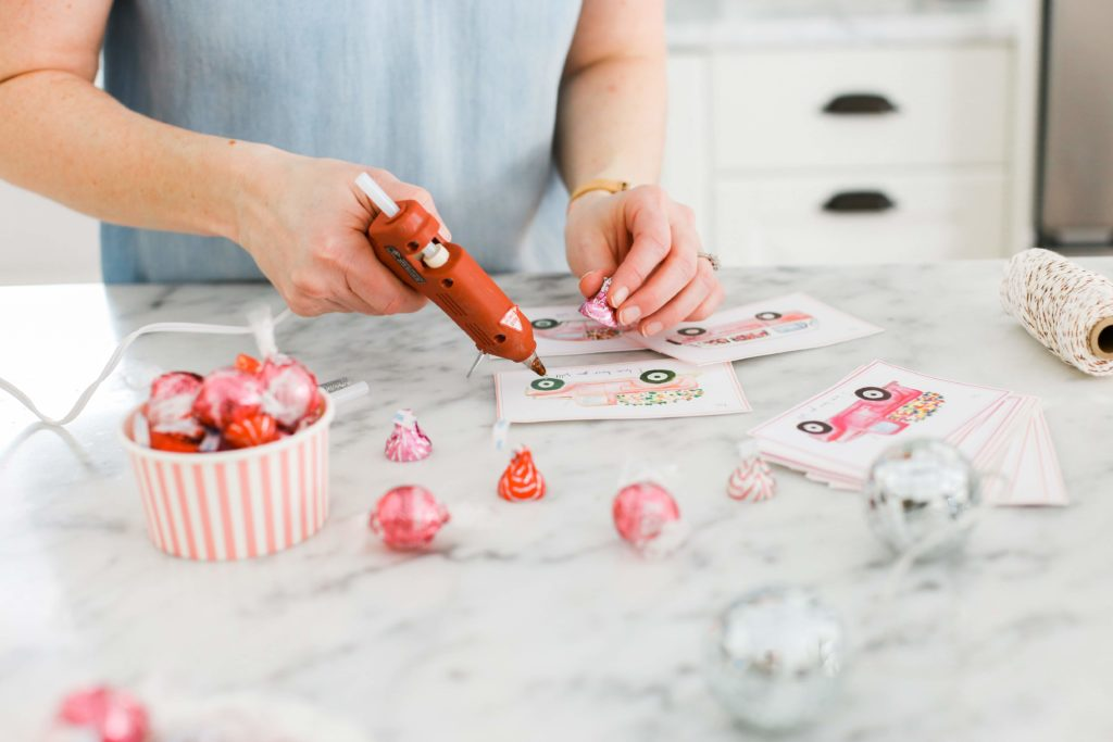 glueing candy onto wheels of cars on Valentine\'s day cards