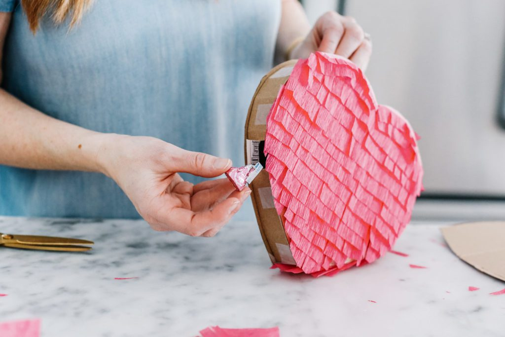 putting candy into a heart pinata