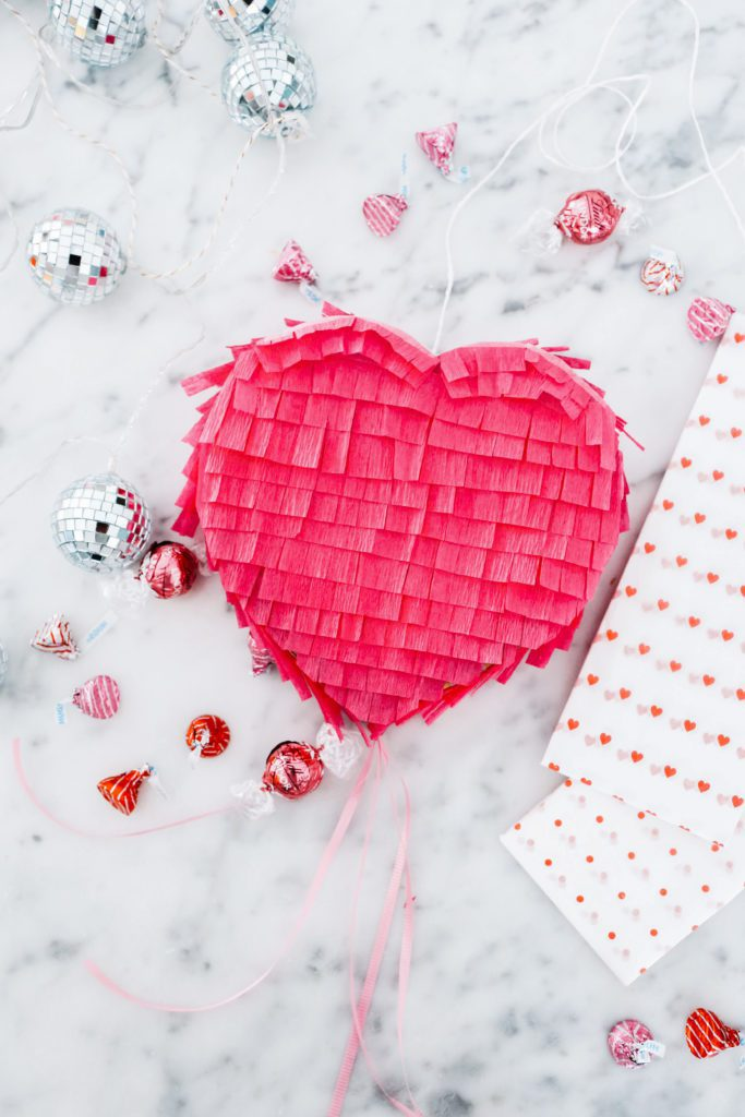 mini heart pinata and candies on marble counter