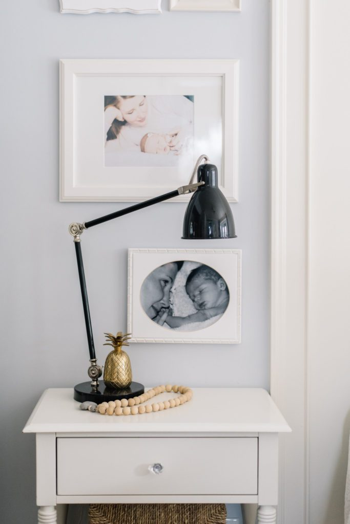 A black industrial style lamp acts a a bedside light on a white farmhouse style side table in a master bedroom.