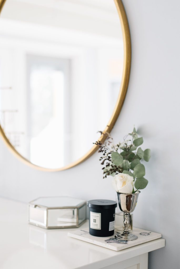 A simple silver vase of fresh flowers sits under a gold framed mirror on a white dresser in a master bedroom