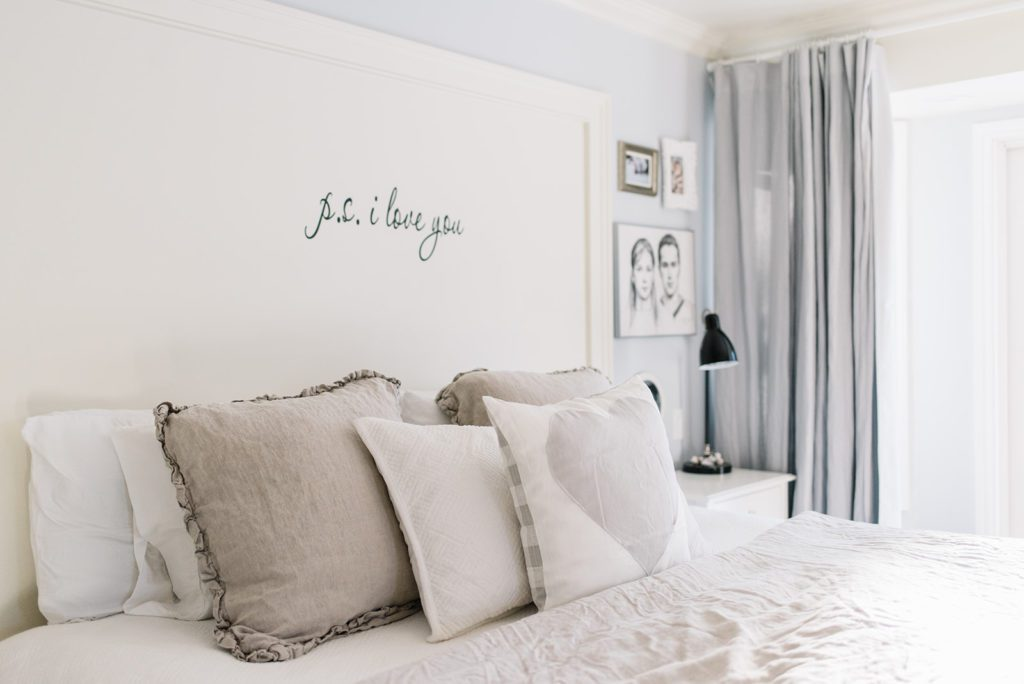 Layered pillows on a king size bed in a small master bedroom