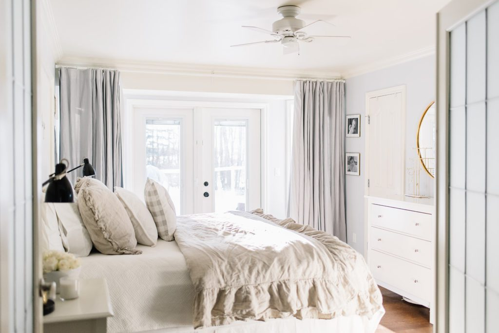 A king size bed with linen bedding and bedding with pillows in a bright master bedroom with patio doors.