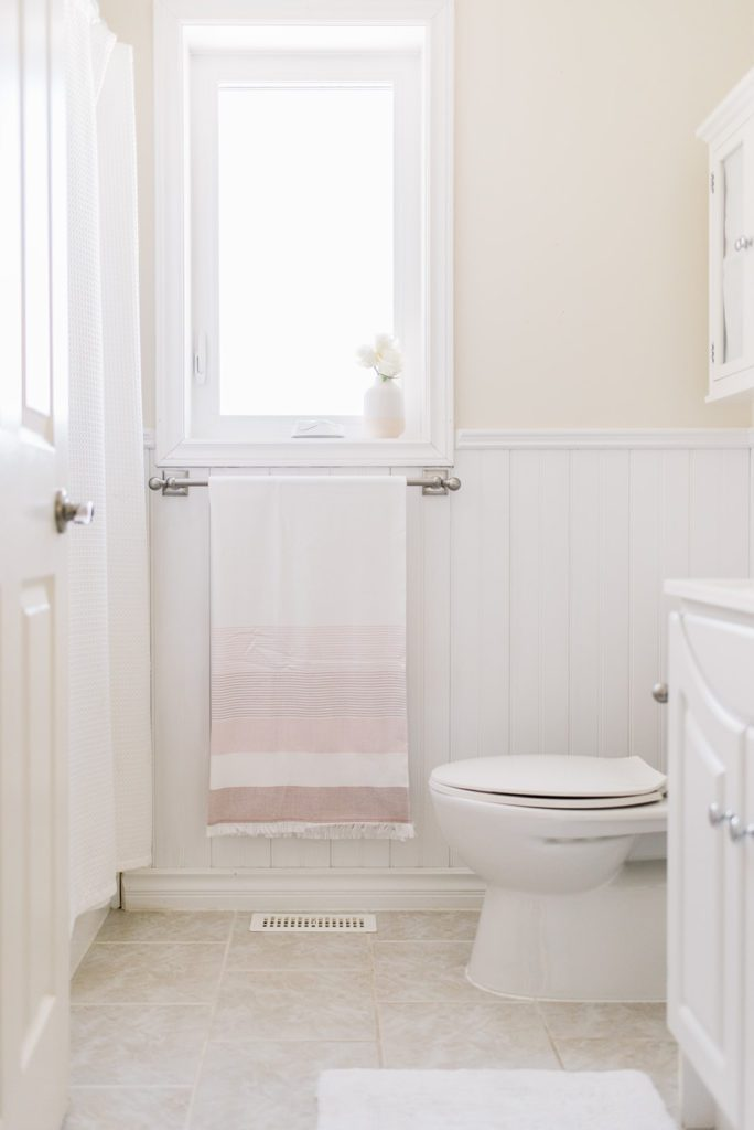 A neutral bathroom with a pink turkish towel
