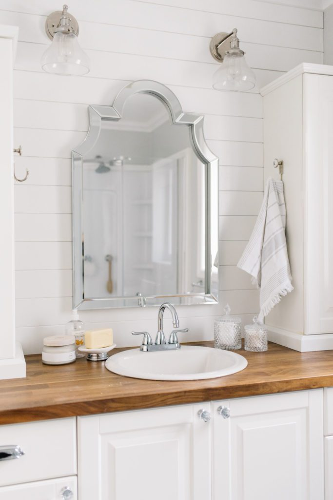 Updated bathroom vanity with wooden countertops and large silver mirror
