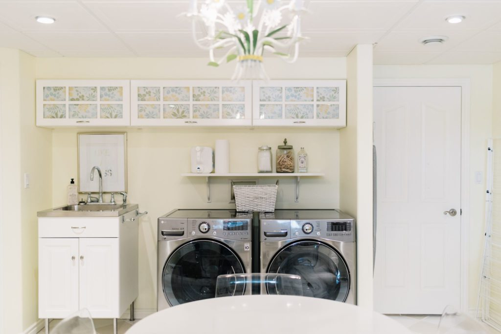 laundry room with built in storage cabinets and yellow walls