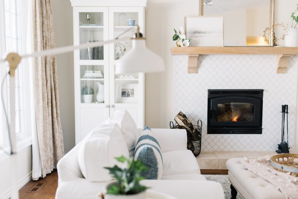 A living room with white couches and a fireplace