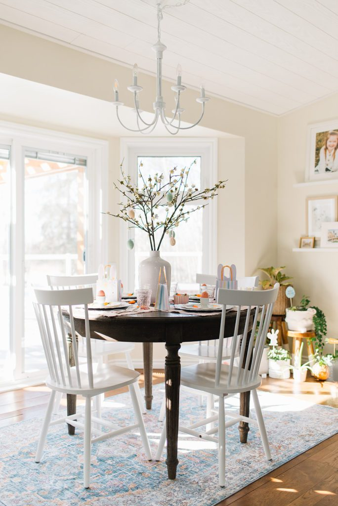 A dining room table with a vase filled with pussy willows
