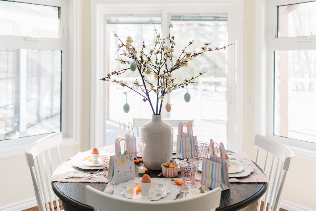 A kids easter tablescape set up with an Easter tree made from pussy willows and hanging Easter eggs