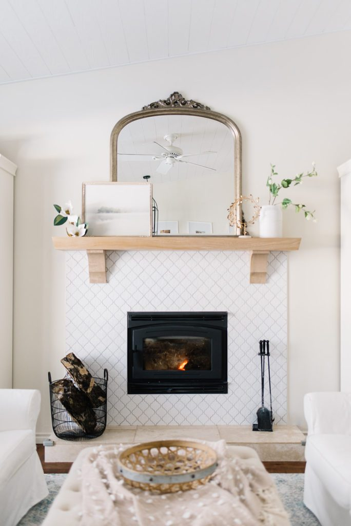fireplace with white tile and white oak mantle with gold mirror