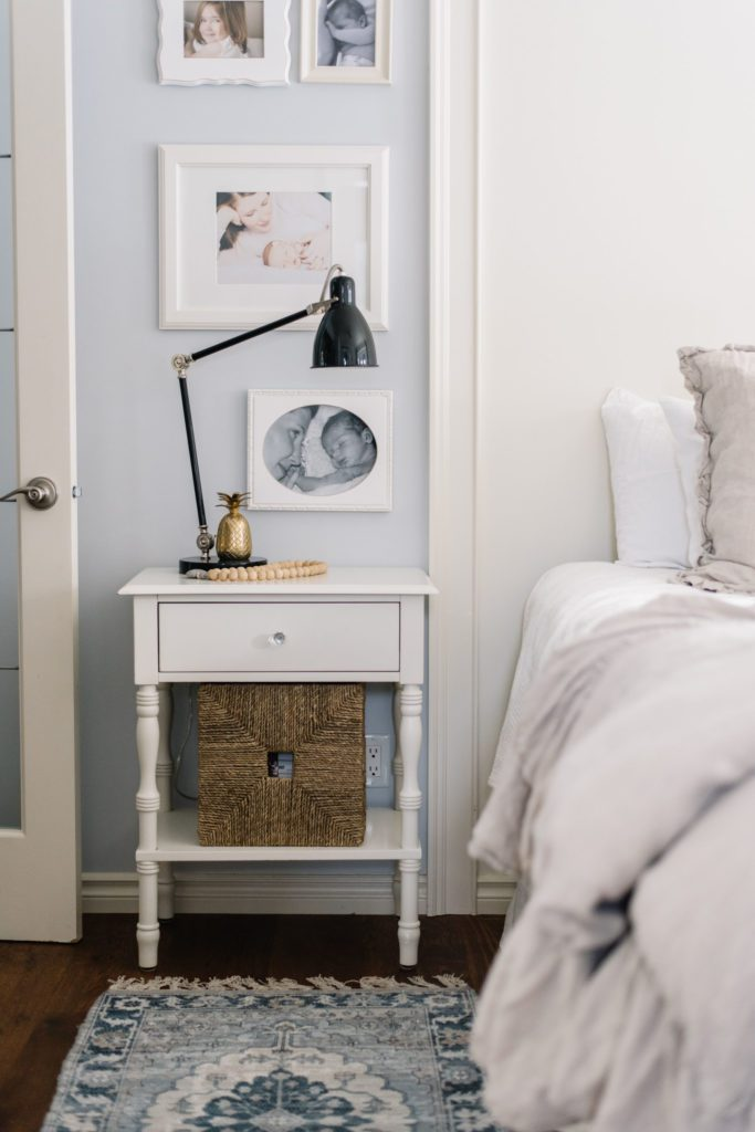 white side table beside bed with black lamp and wicker basket