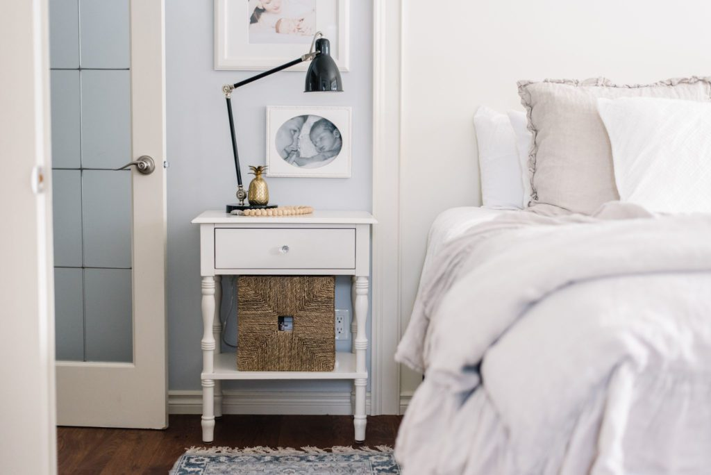 A white bedside table with a basket for storage beside a bed in a small master bedroom