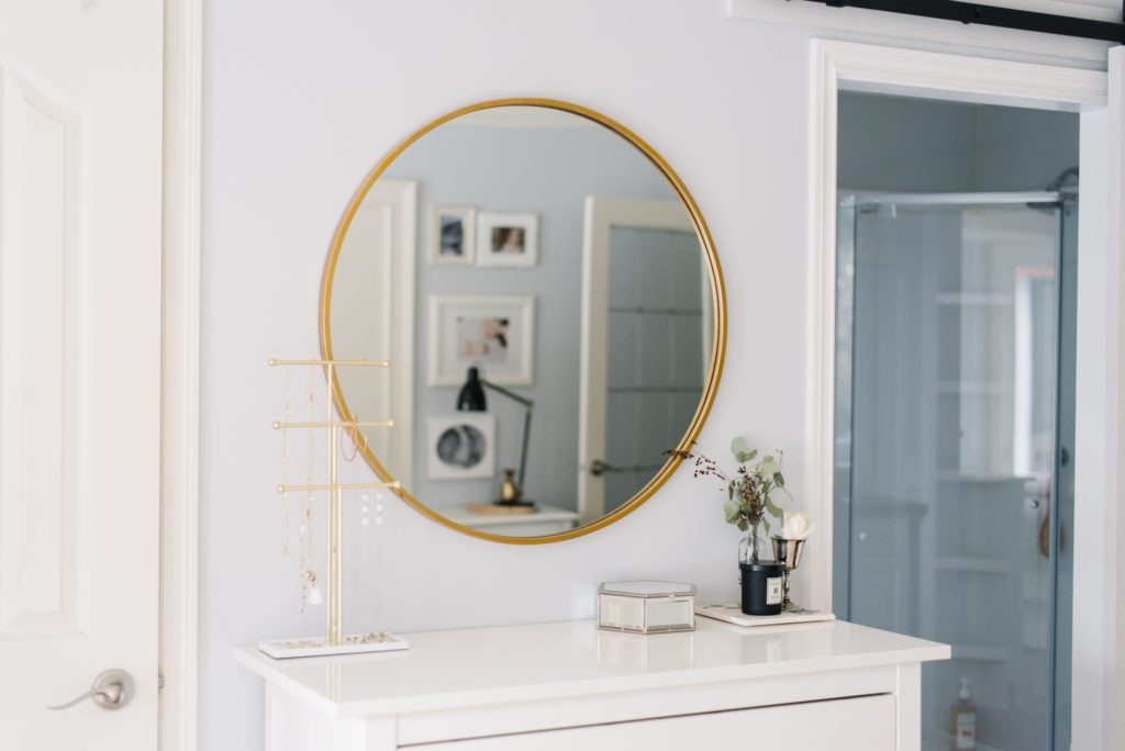 A gold framed round mirror above a white dresser bounces light into a small master bedroom
