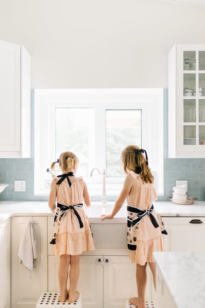 girls at the kitchen sink wearing aprons