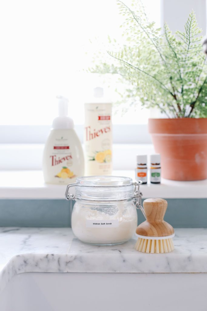 A jar of natural cleaner sitting on a counter beside a scrub brush