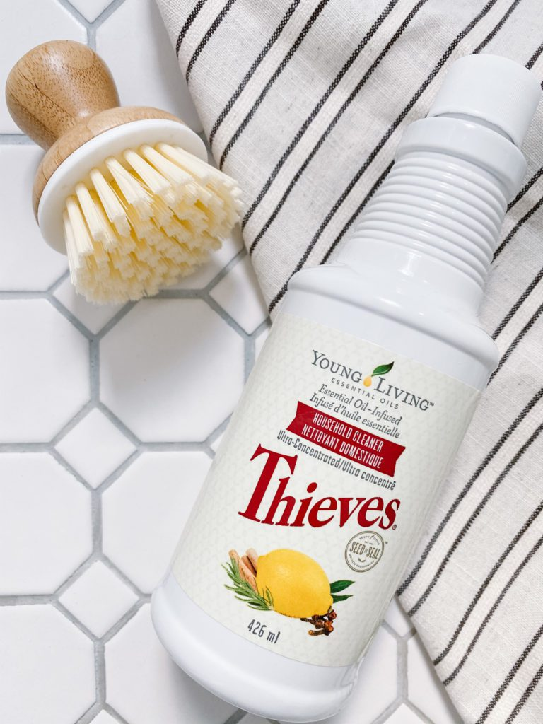 A bottle of Thieves cleaner and a bamboo scrub brush
