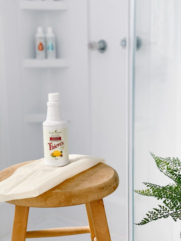 A bottle of cleaner on a stool in front of a glass shower
