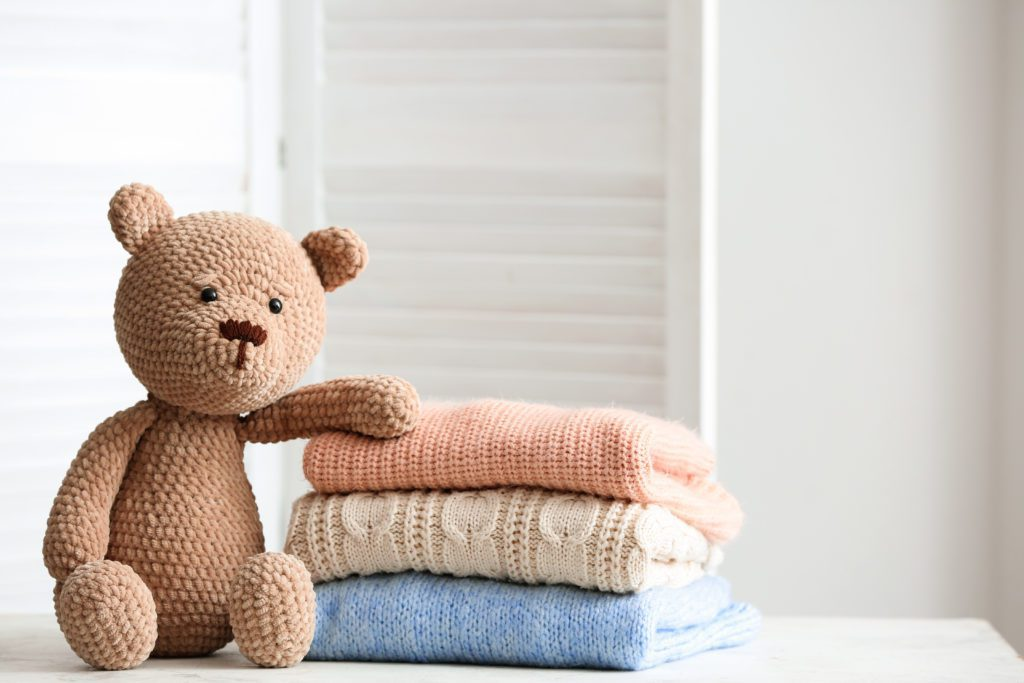 stack of sweaters next to a teddy bear