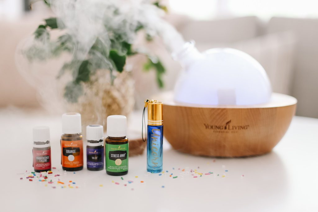 essential oils and a roller in front of a Young Living Aria diffuser