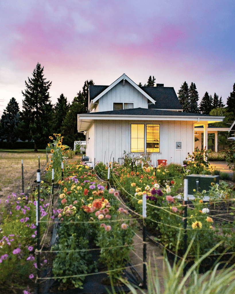 A close up of a flower garden in front of a farmhouse