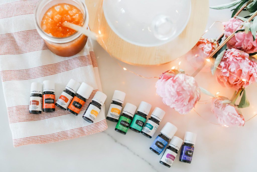 a rainbow of essential oils in front of a glass diffuser