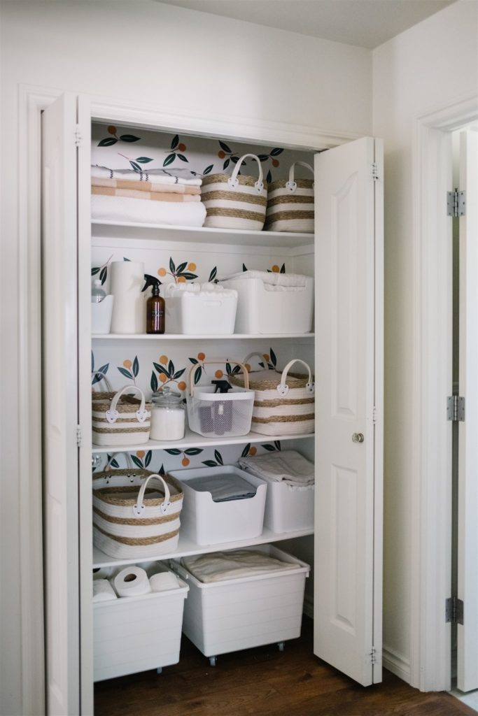 linen closet with orange pattern wallpaper and white baskets