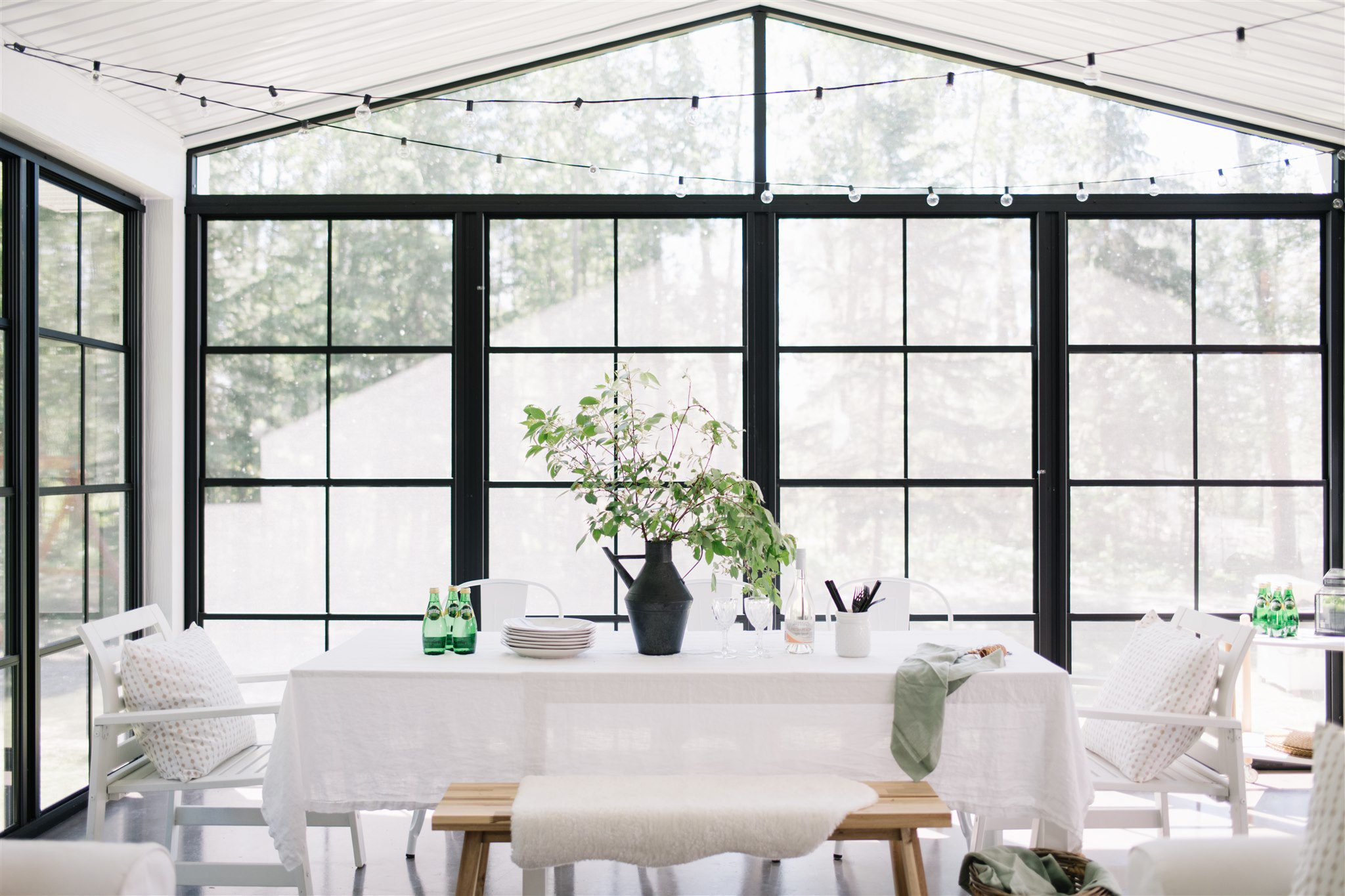 dining room table in an outdoor screen room with patio lights above