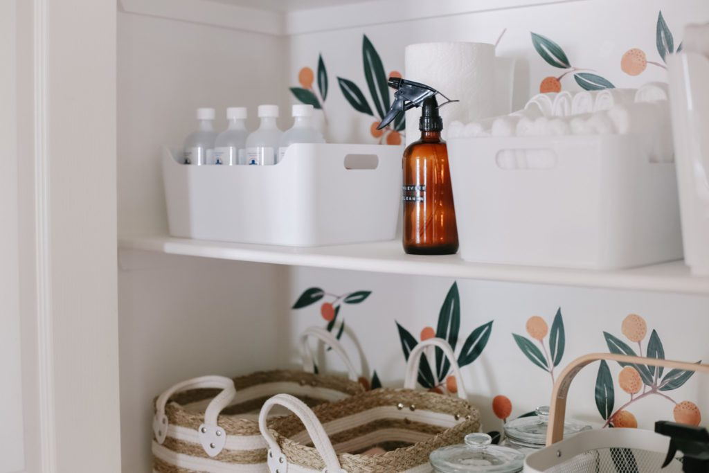 amber bottle and white bins in linen closet