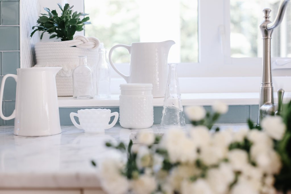 an assortment of white vases, pitchers and containers
