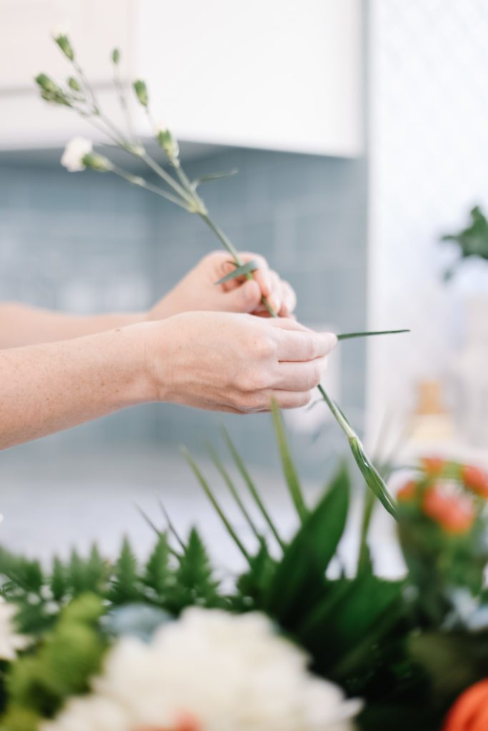 pulling extra leaves off flower stems