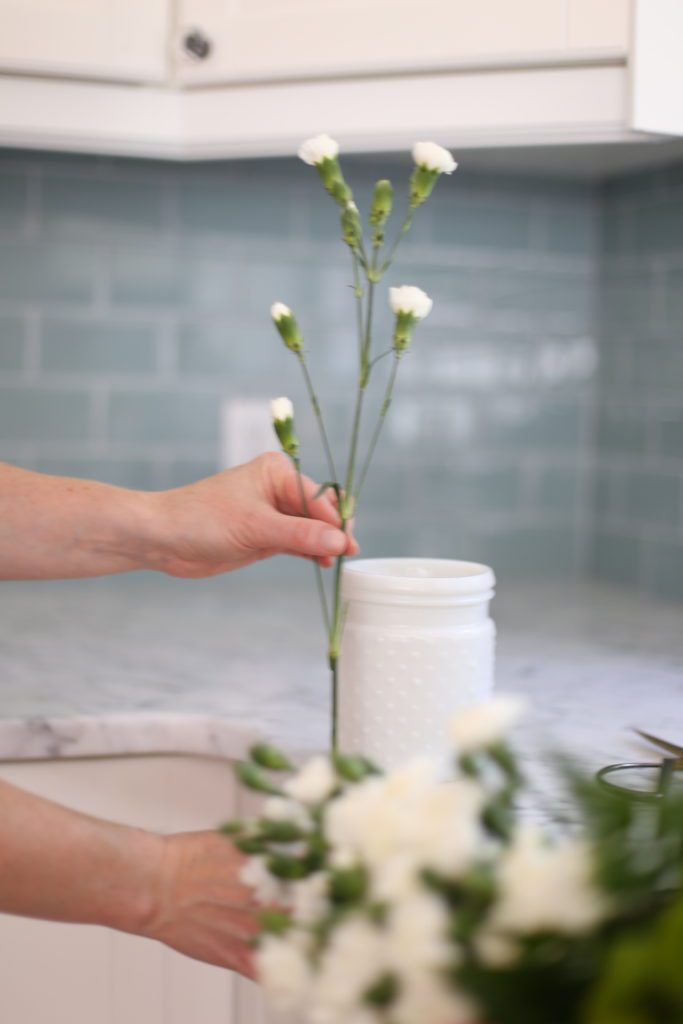 holding flower stems up beside a vase to see how long to cut the stem