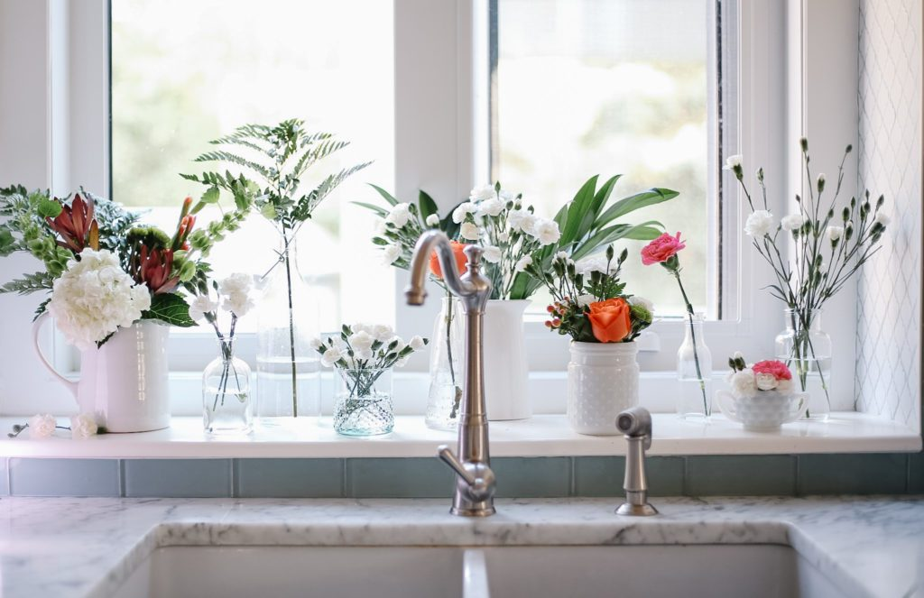multiple floral arrangements lined up on kitchen window sill