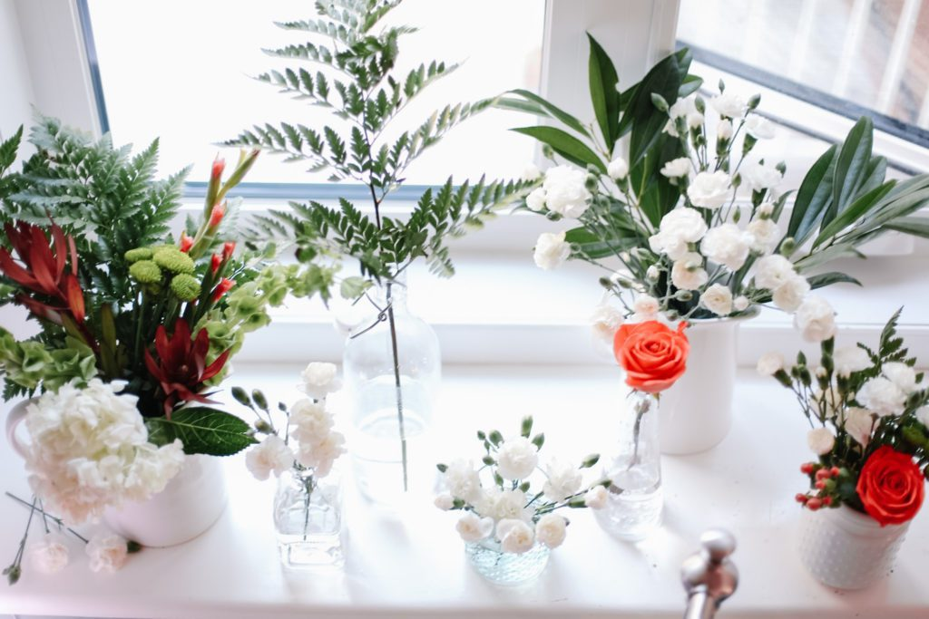 lots of different sized floral arrangments in different vases and vessels
