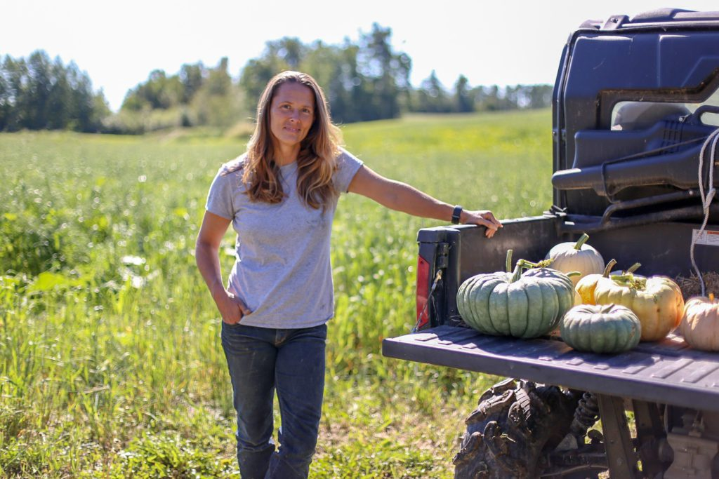 A woman standing in a field with pumpkins in the back of a truck