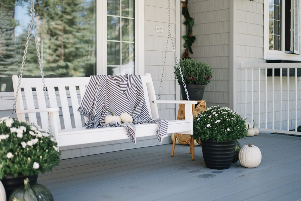 front porch swing with fall mums and white pumpkins