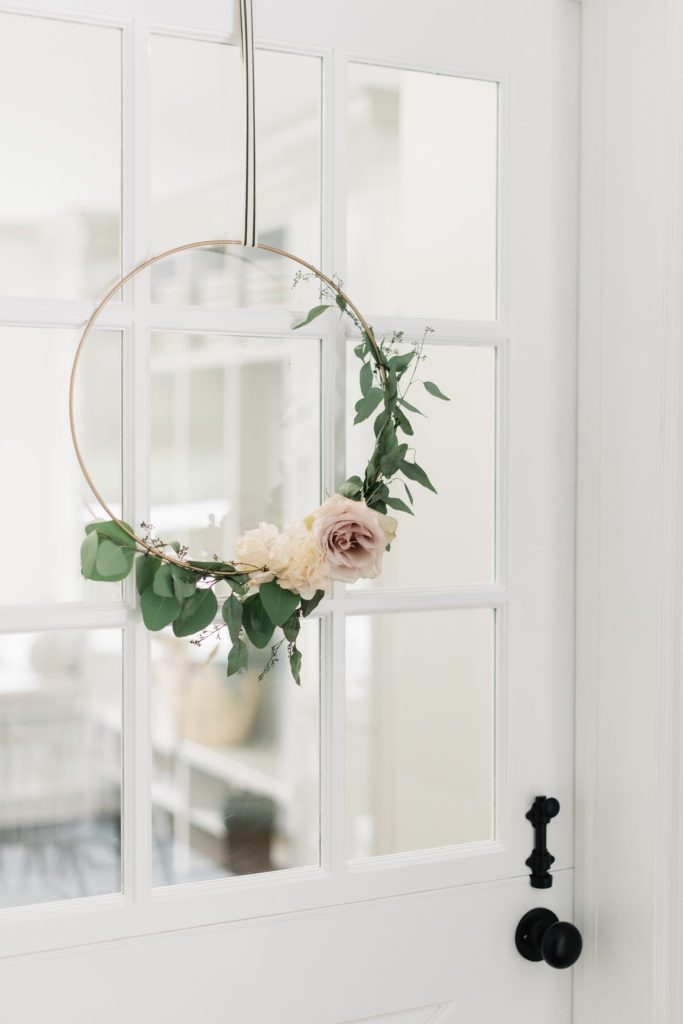 a floral hoop hanging on a glass window