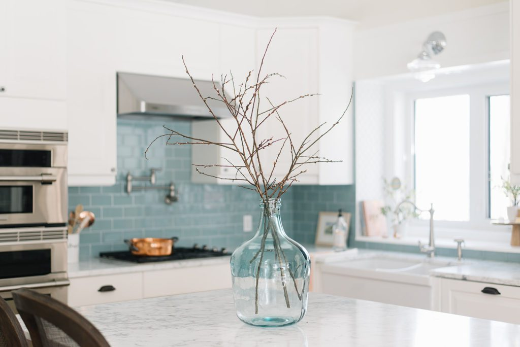 large glass vase with branches in kitchen