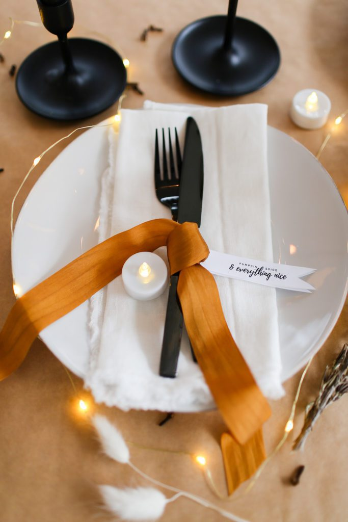 place setting with white plate and napkin, black cutlery and bronze silk ribbon
