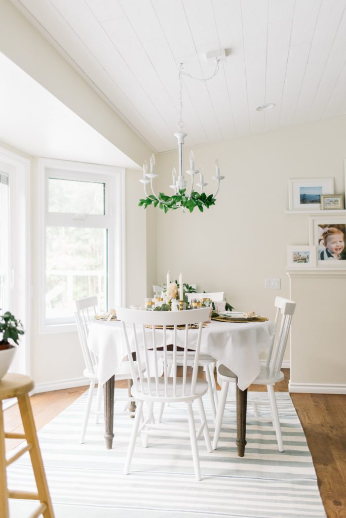 A dining room table with greenery on the chandelier above it
