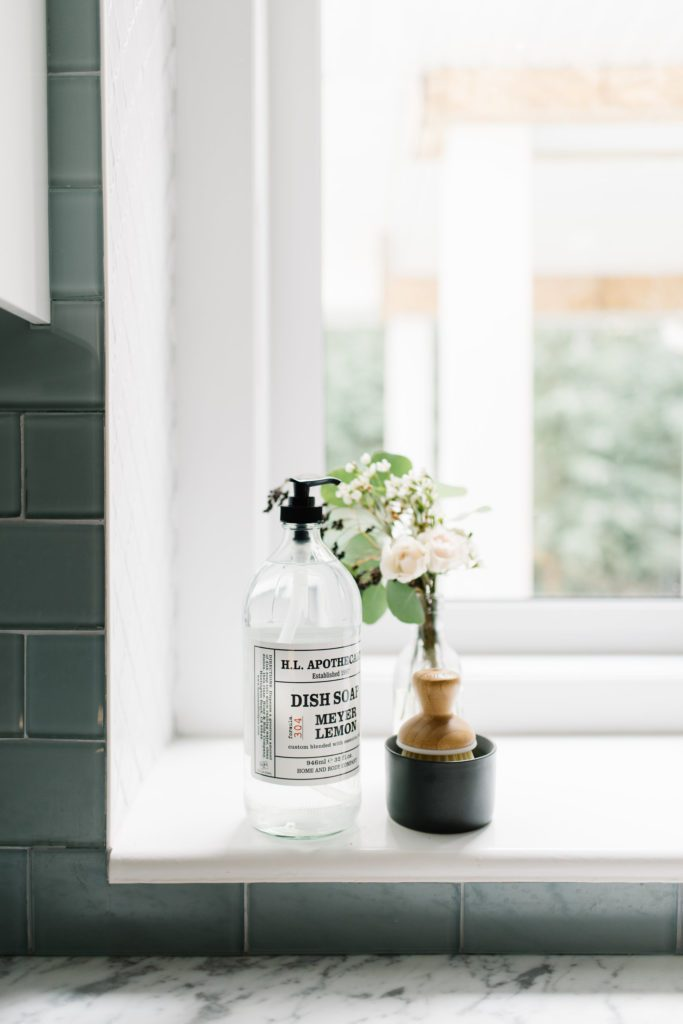 bottle of handsoap and scrub brush on kitchen window sill
