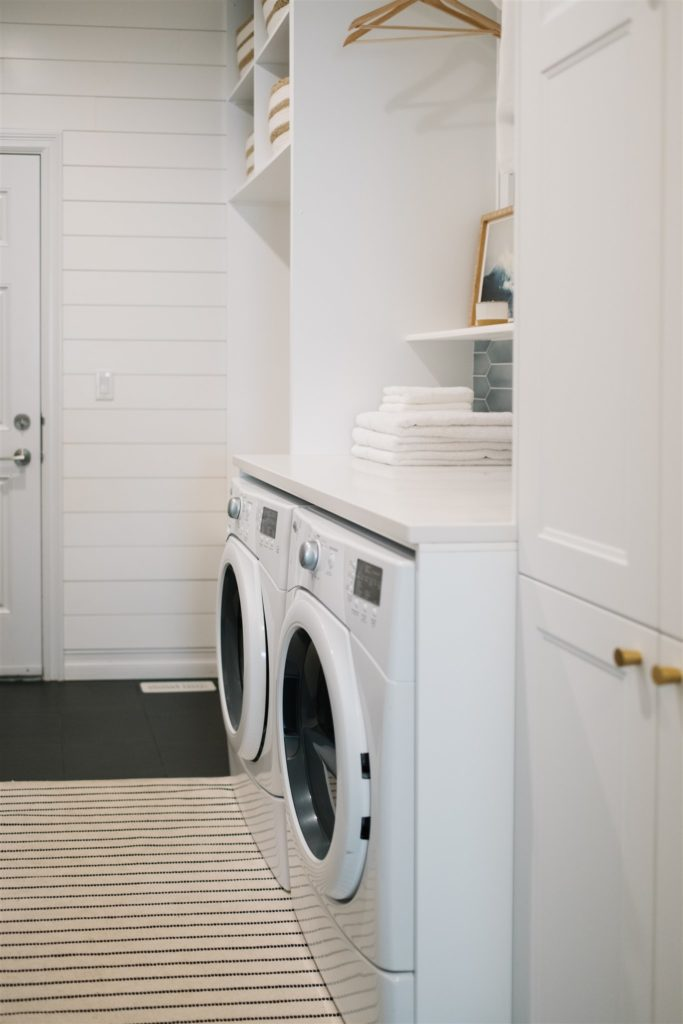 a washer and dryer with white stone countertop