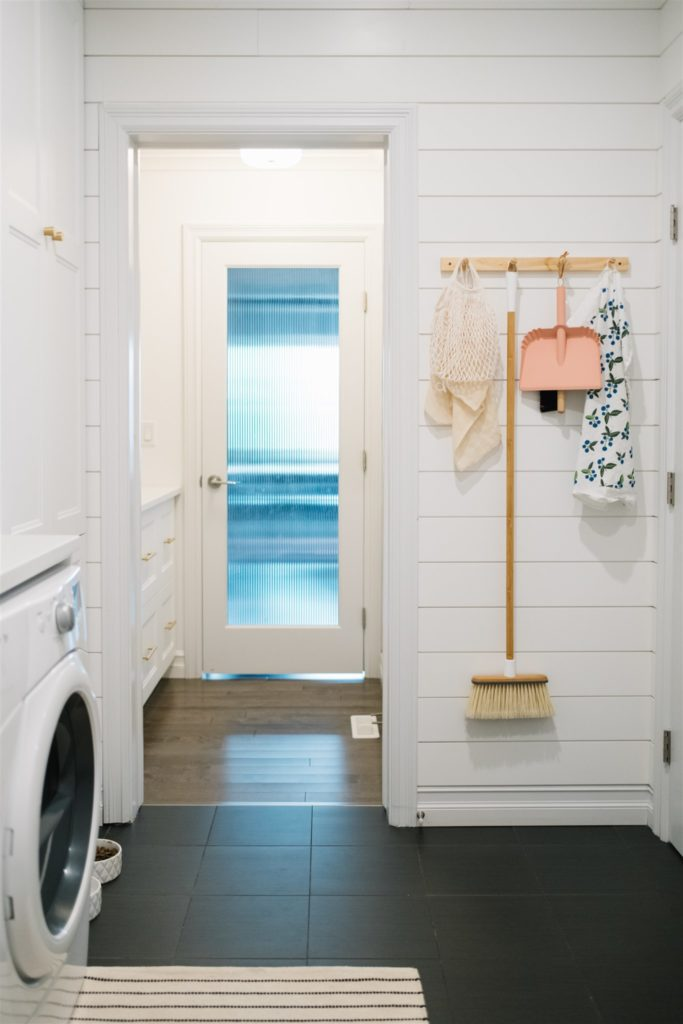 peg rail with brooms and utility items hung up