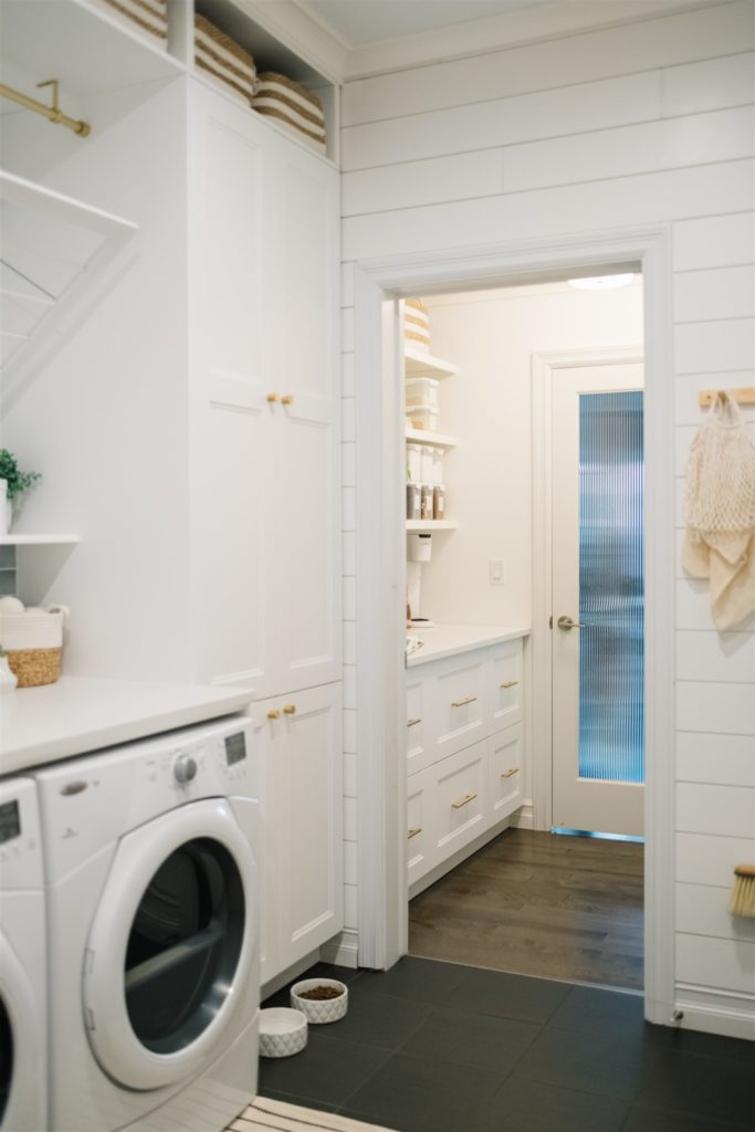 renovated mudroom and pantry space with white cabinets and gold accents