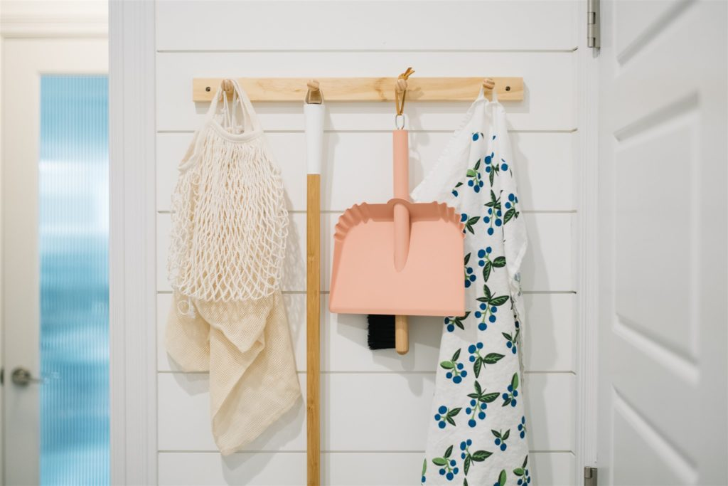 peg rail with pink dustpan hanging on it