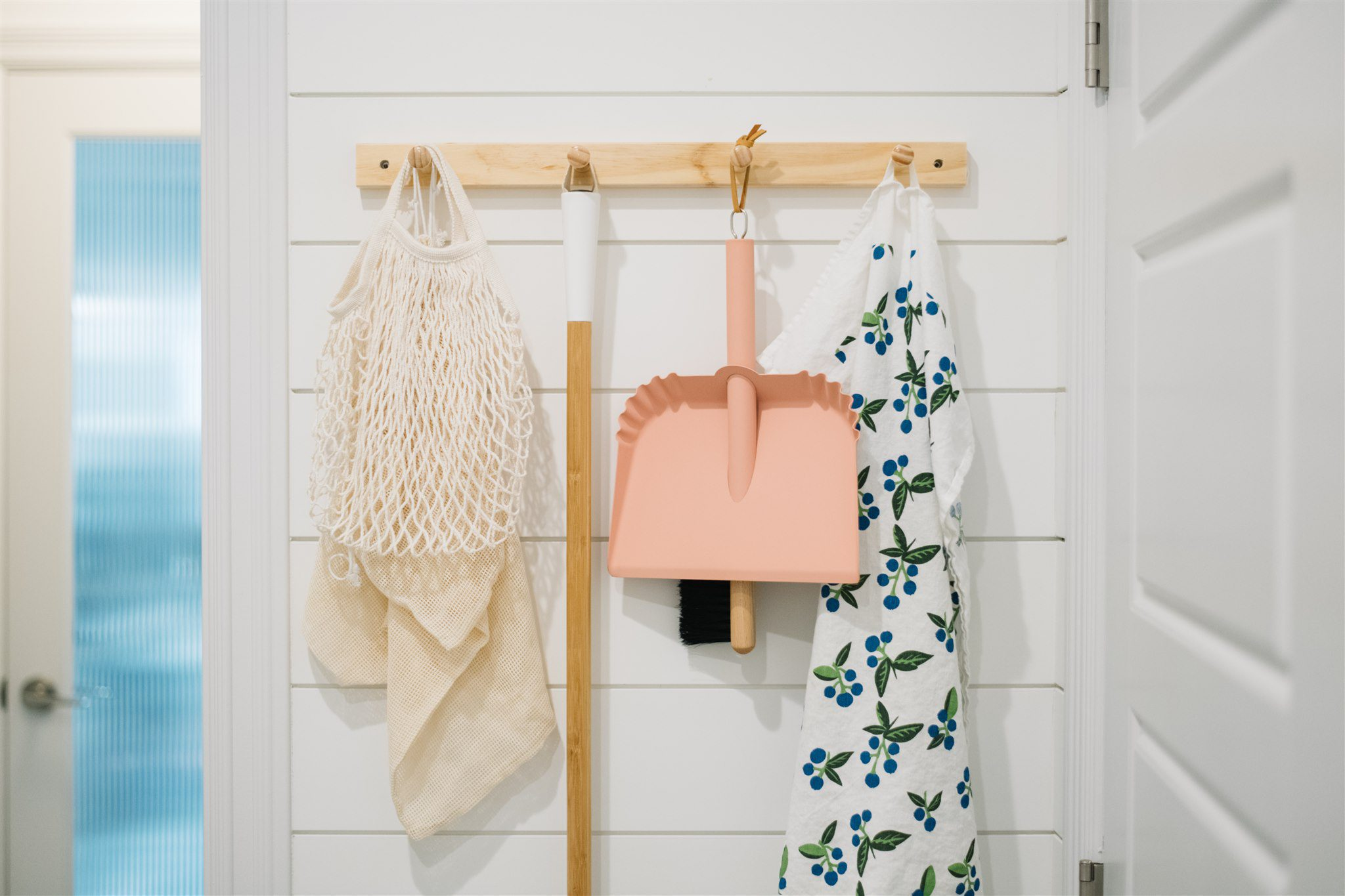 peg rail with dustpan, tea towel and market bags hung on it