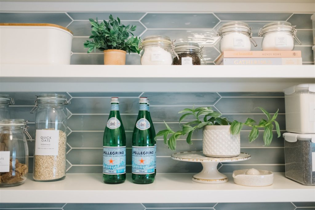 bottles, containers and plants on open shelving
