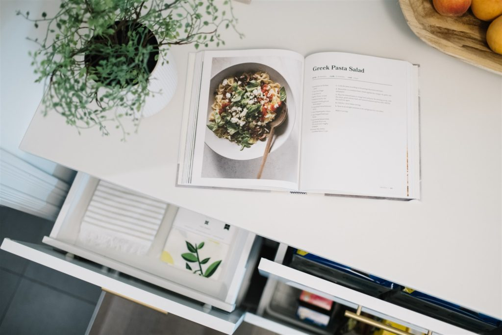 A cookbook sits open on a kitchen counter