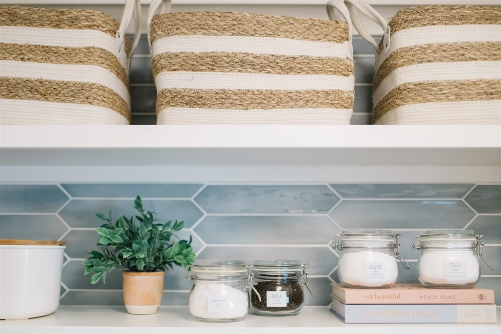 woven baskets on a shelf in a pantry